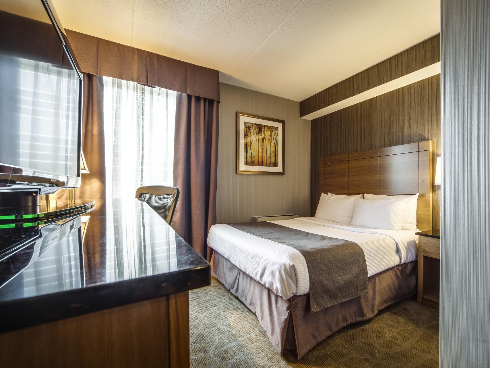 Double bed with flat tv, working table and chair - Monte Carlo Inn Airport Suites