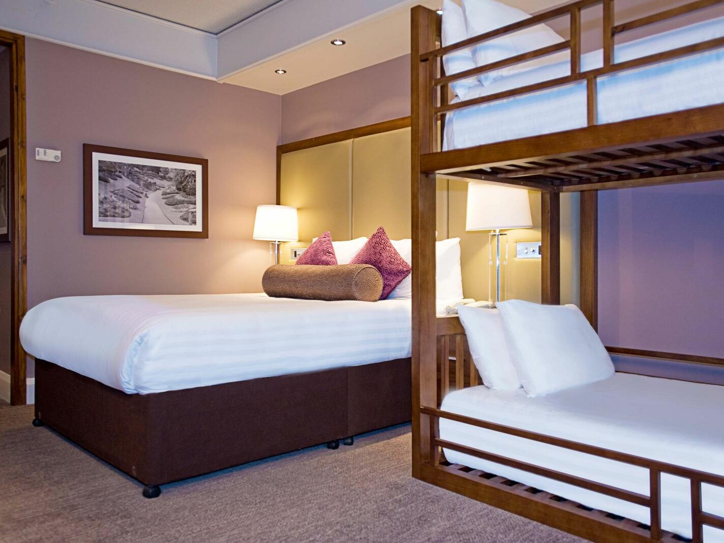 The Family King Room at Sandman Signature London Gatwick Hotel with one king bed (with premium pillow-top) and two bunk beds