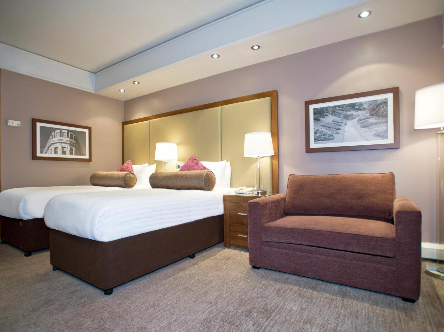 The Triple Room at Sandman Signature London Gatwick Hotel with two single beds (with premium pillow-top) and a one seater sofa on the side