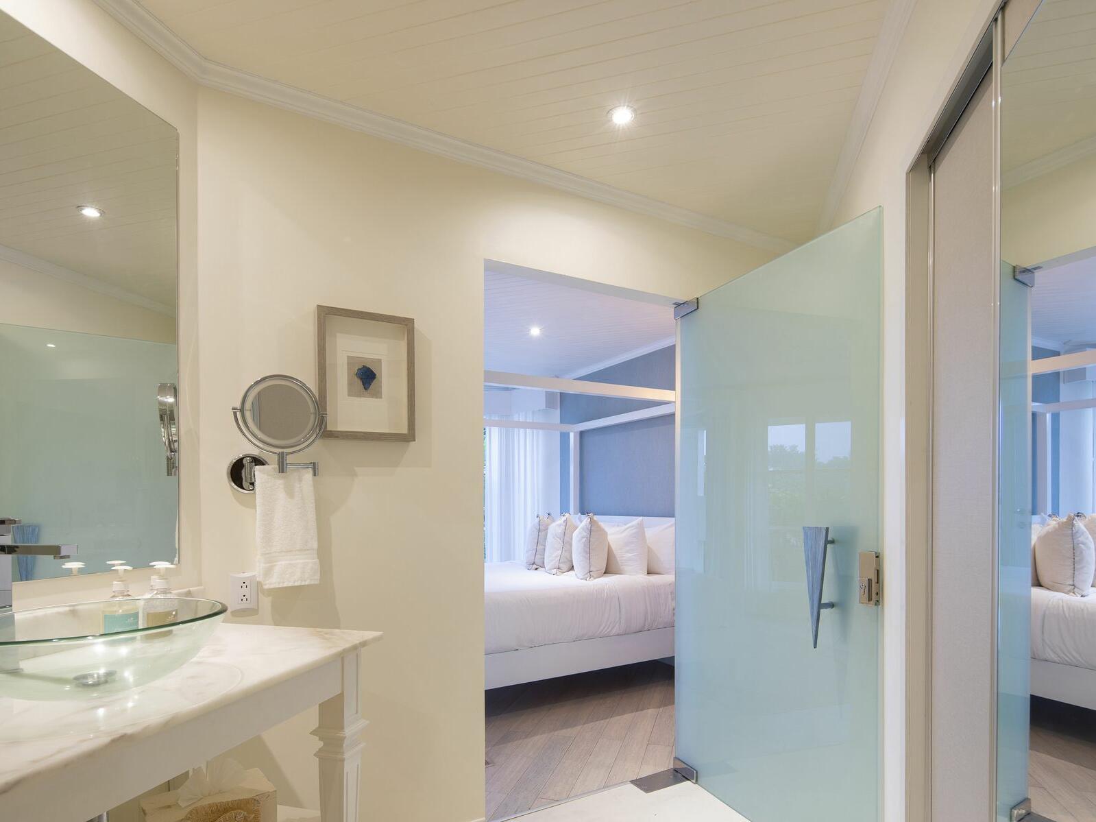 hotel bathroom with vanity and door to bedroom