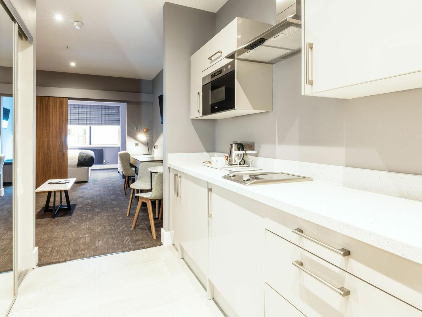The Pantry with White Pantry Cupboards and with Kitchen Supplies and White Furniture in the Corporate King Suite at Sandman Signature Aberdeen Hotel