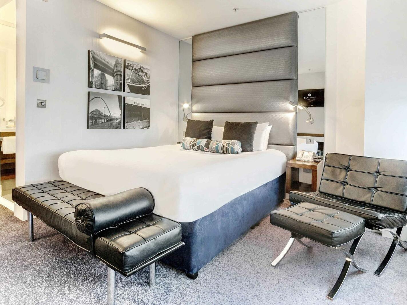 The King Room at Sandman Signature Newcastle Hotel with one king bed (with premium pillow-top) with a two seater black leather chair on the side of the bed with a foot rest