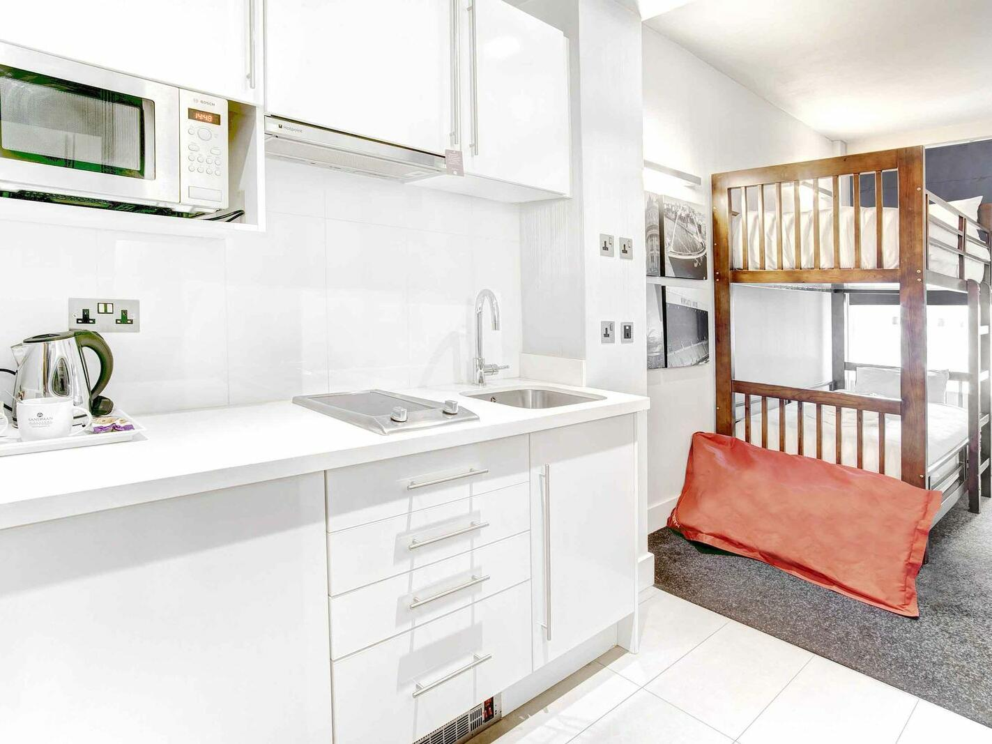 The Family King Suite at Sandman Signature Newcastle Hotel with two bunk beds and a pantry with kitchen supplies and white pantry cupboards