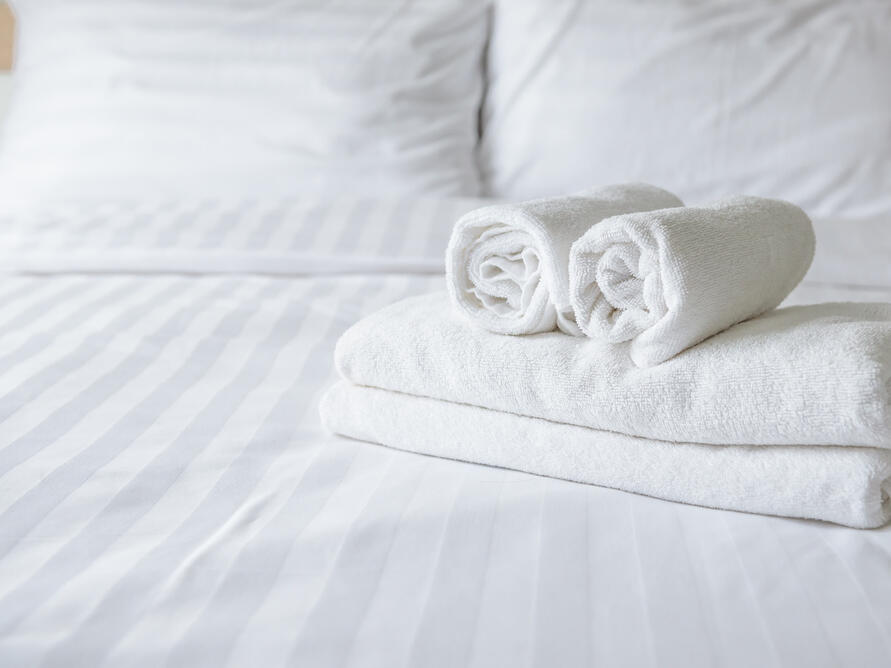 Towels on guests' bed at Amora Hotel