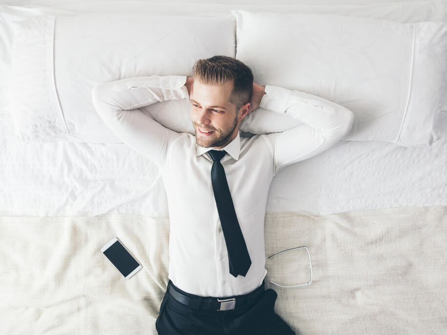 Guest on bed wearing formals at Amora Hotel