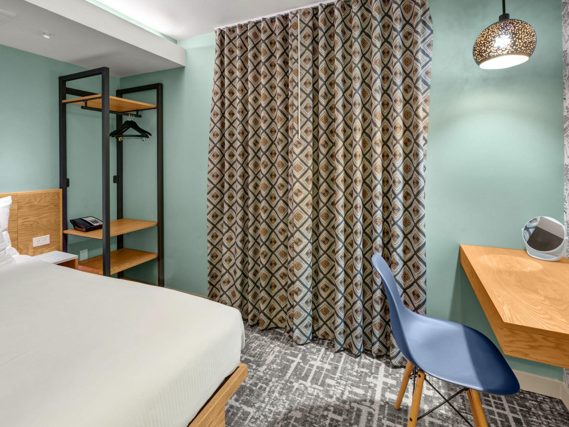 hotel keen guest room with desk, closet organizet and bed