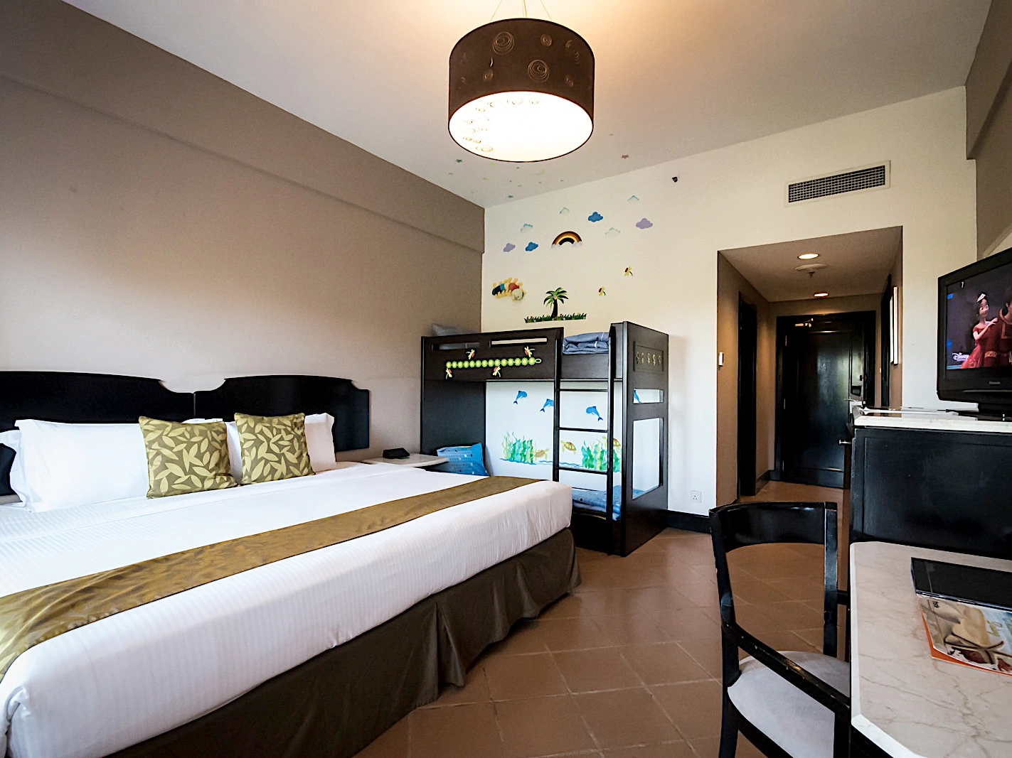 The Thistle Family Deluxe Room with one king bed, a double decker bed, a desk, a chair and flat- screen TV at the Thistle Port Dickson Resort