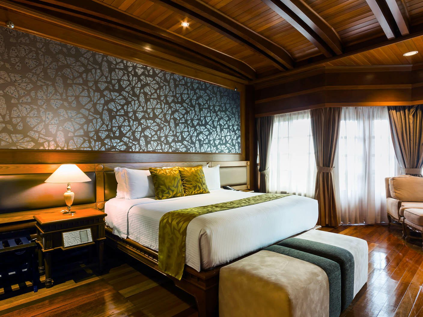 The Presidential Suite with one king bed, a chair and side table at the Thistle Port Dickson Resort