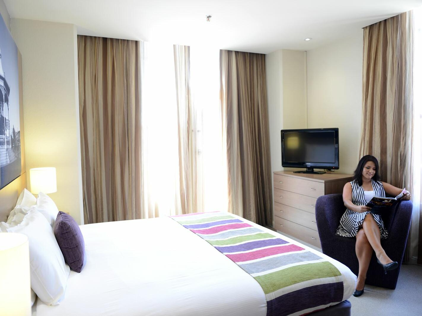 Suites room with a lady reading a book  at Grosvenor Hotel