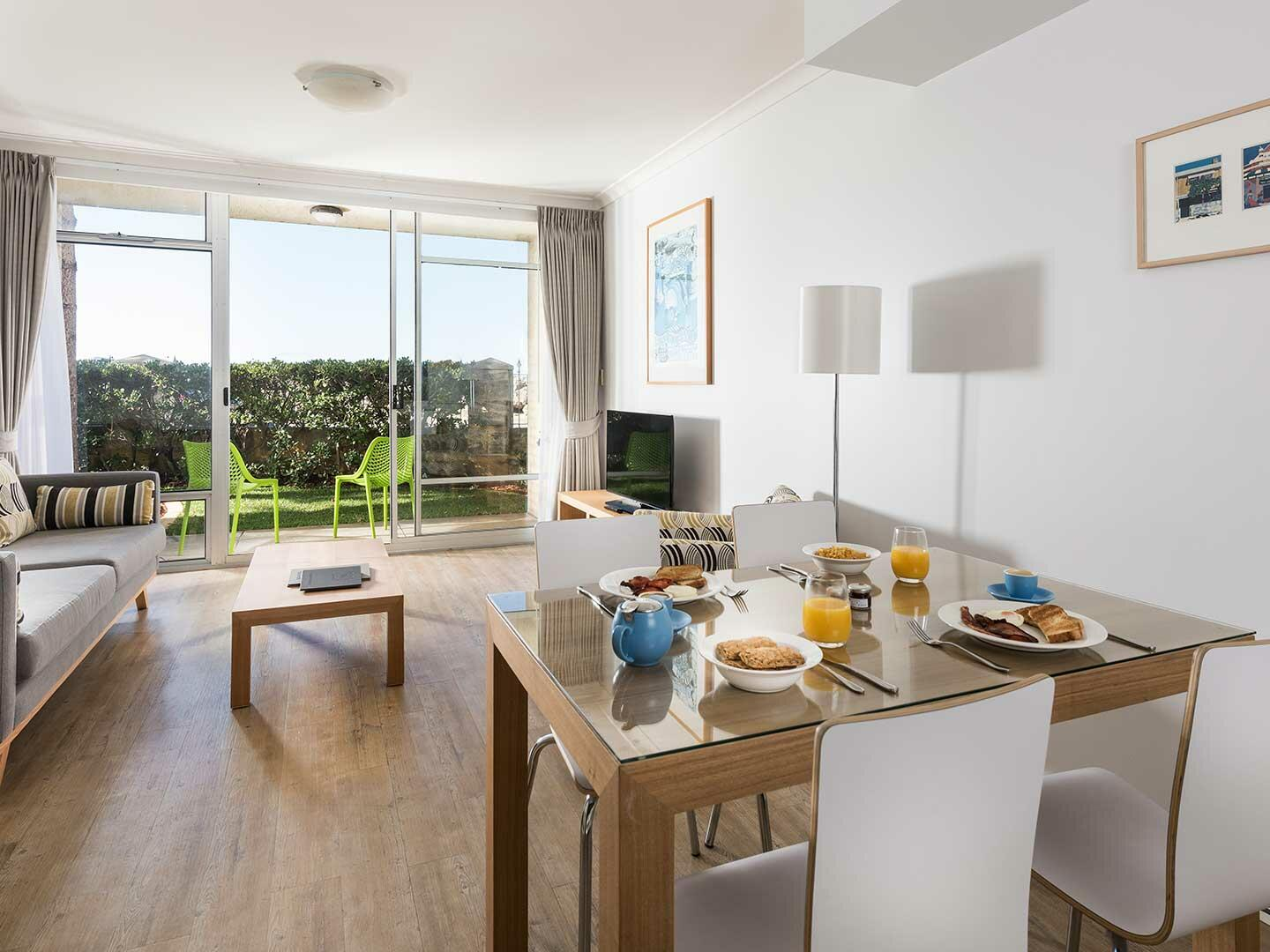 Living area and dining area in 2 Bedroom Harbour Sunrise Spa apartment at Be Fremantle