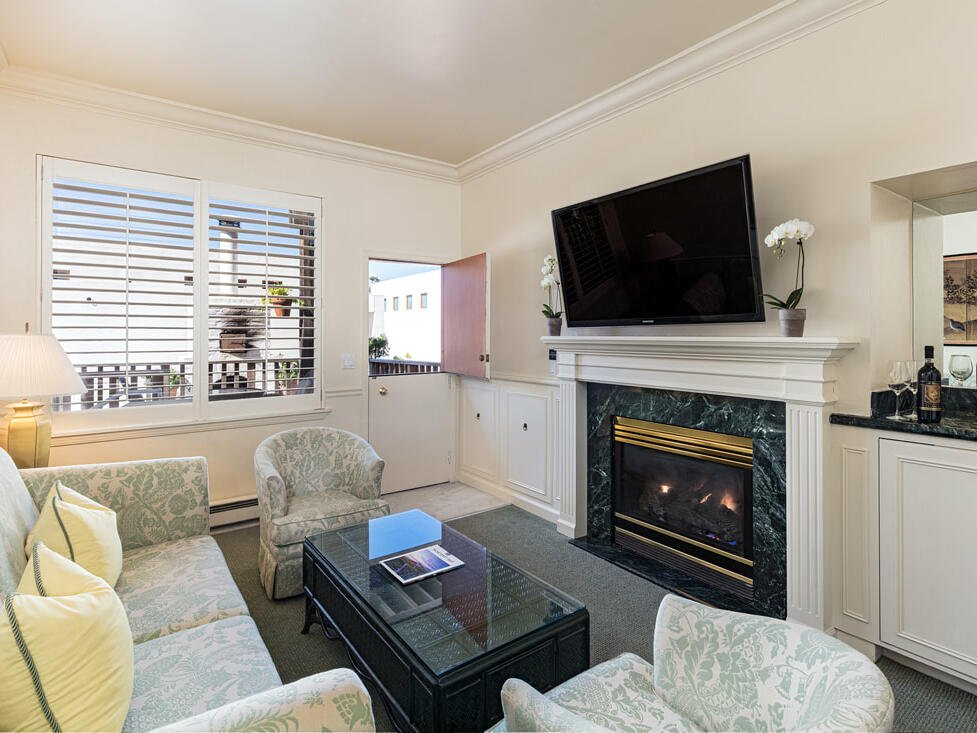 Double Queen Suite living room with sofa and TV at Tally Ho Inn