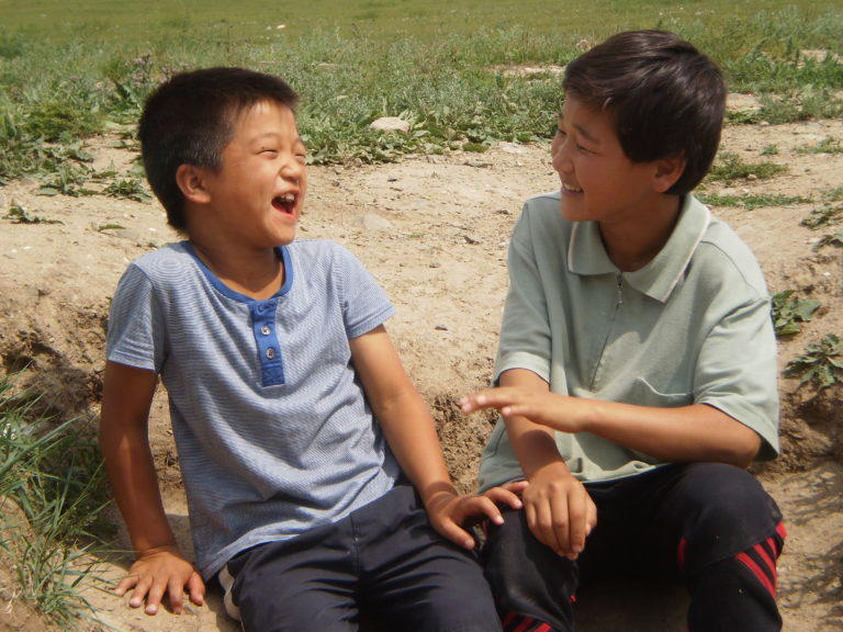 Two kids smiling with each other at Lotus Children's Centre