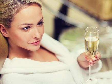 beautiful lady enjoying champagne in robe at Amora Hotel