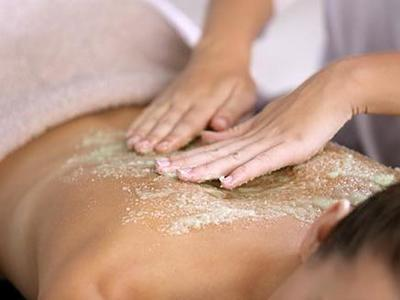 woman having back exfoliation treatment in spa