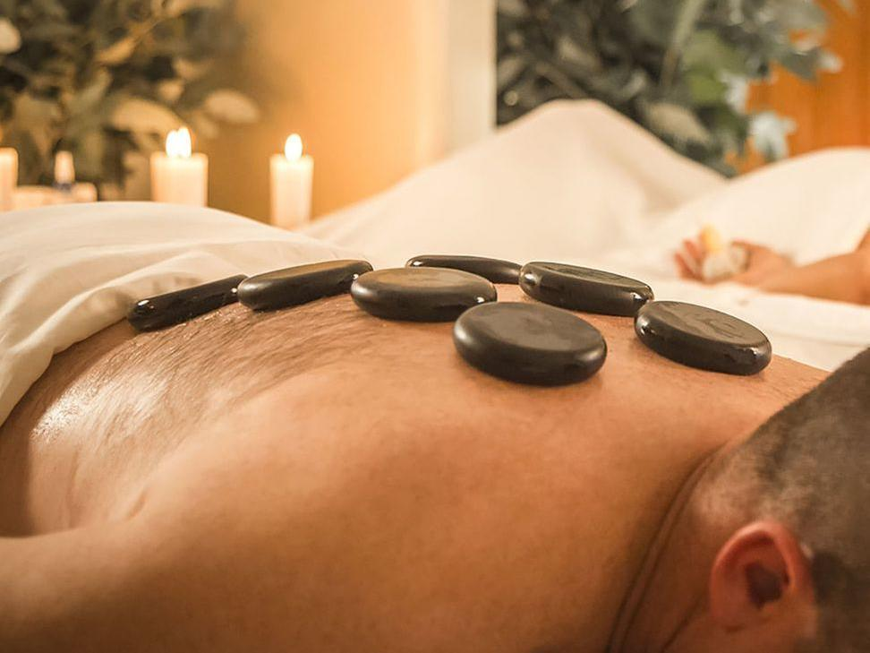 A client having Massage with andean hot stones at Hotel Sumaq