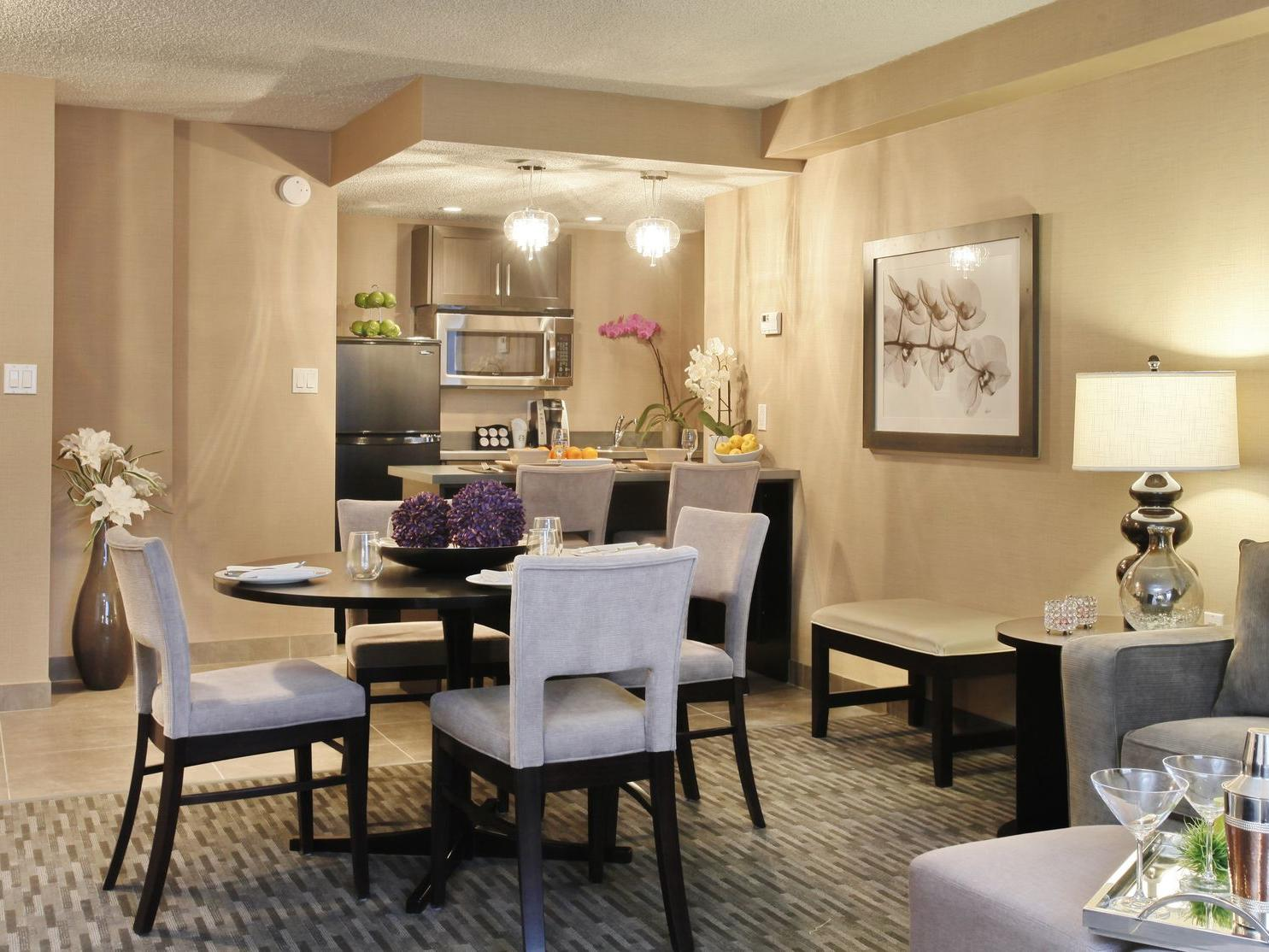 a dining table next to a kitchen in a hotel suite