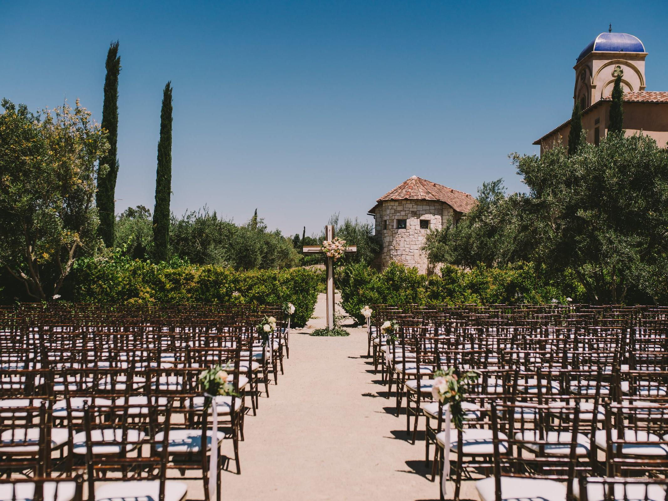 Looking down the aisle of rows of chairs set for an outdoor wedding
