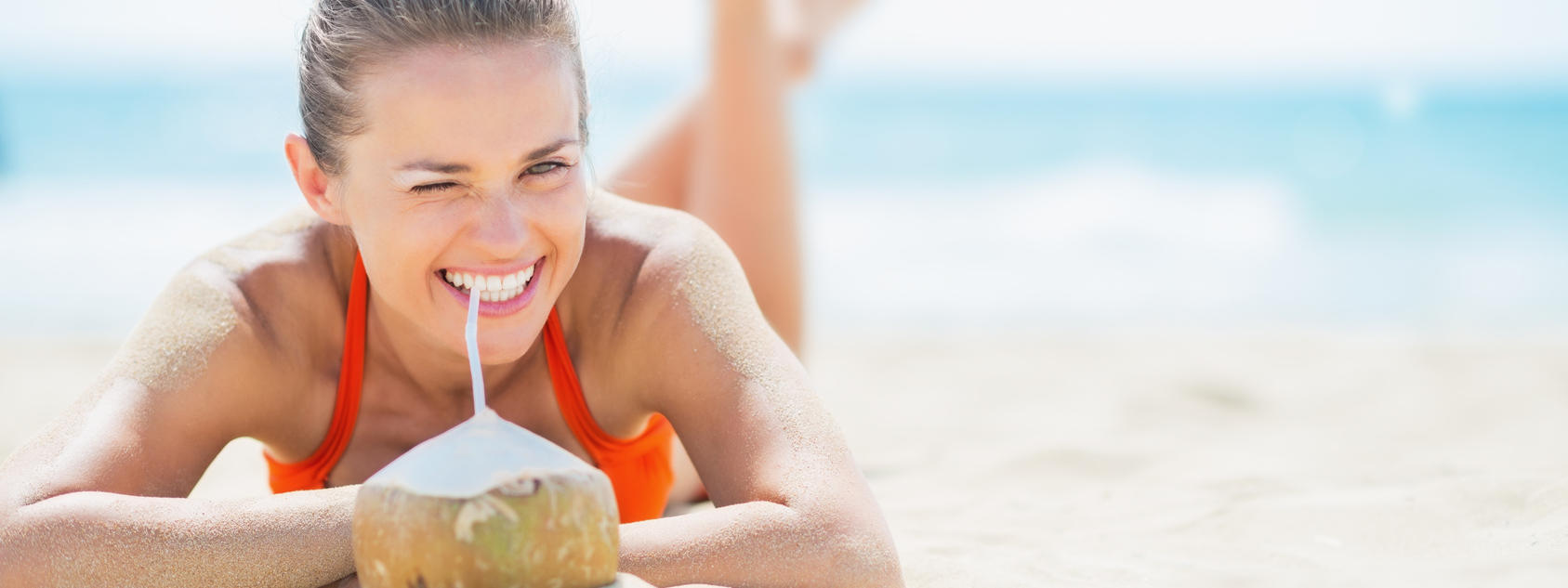 Girl Smiling on Beach Drinking Coconut Water