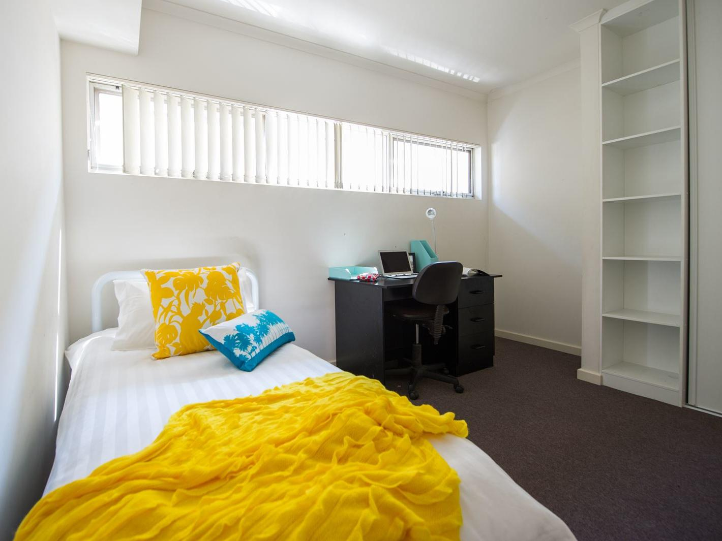 Student Living Edge Apartments – Grote Street Building - Typical bedroom with single bed, study desk & chair & built in wardrobe