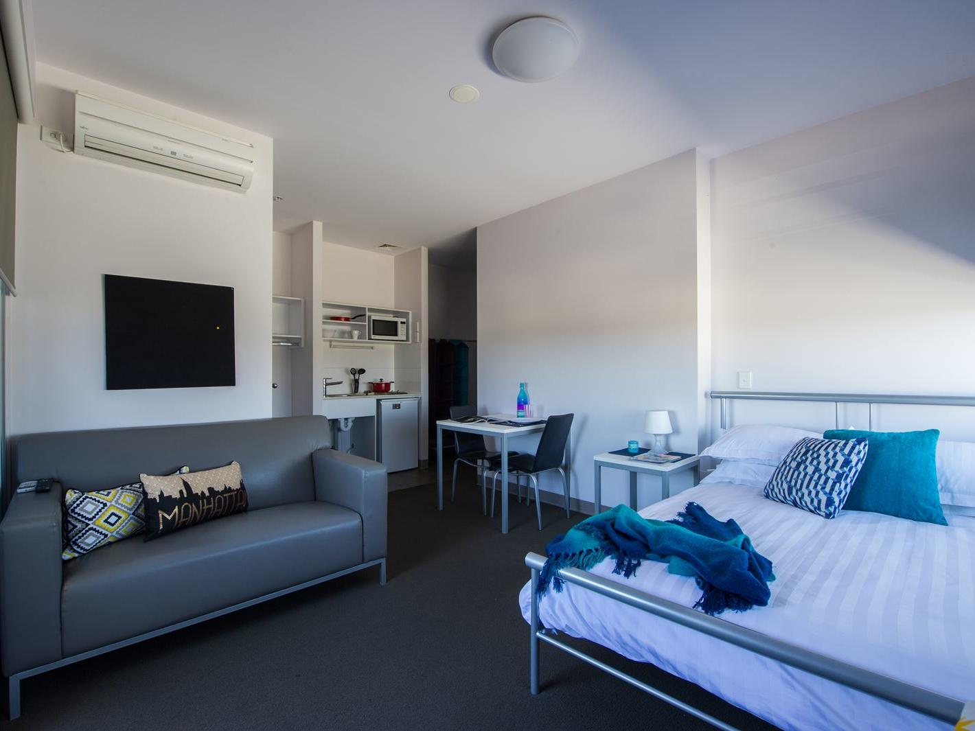 Typical studio double apartment featuring double bed, TV, study desk & chair, bedside table, dining table & chairs, 2 seat lounge, kitchenette & bathroom (not shown) - purchase hotel quality linen via our online shop, Your Shop