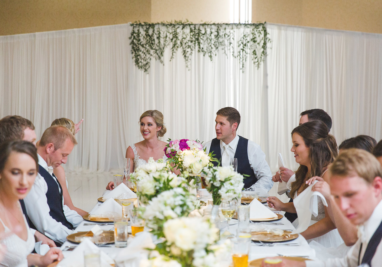 a bride and groom sit at the head of a table