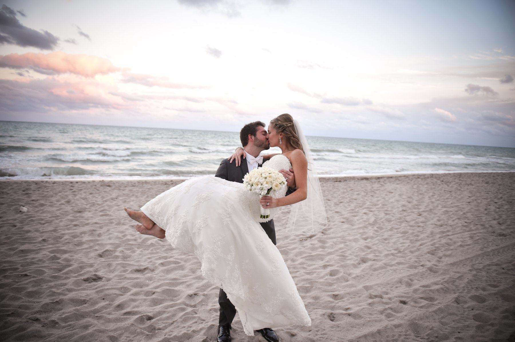 Groom Holding Bride at the Beach