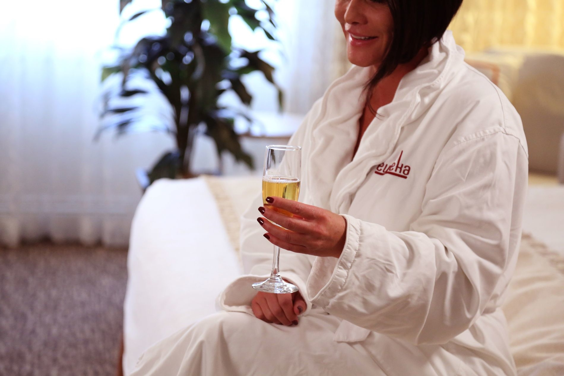 Woman wearing robe sitting on bed holding glass of champagne