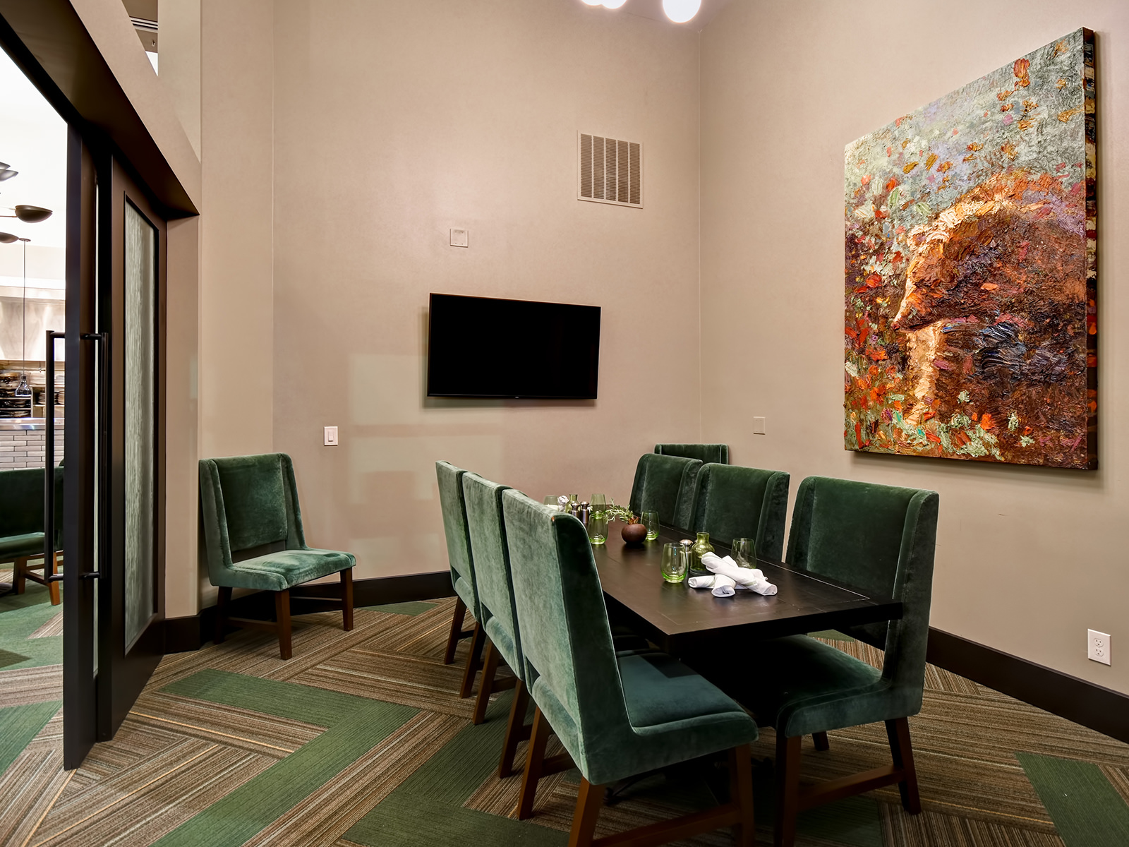a conference table facing a wall mounted tv