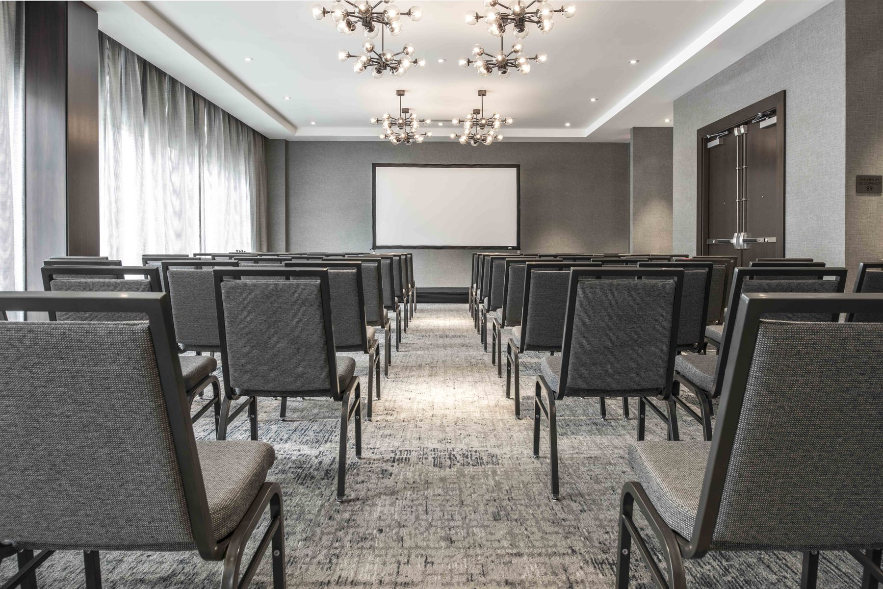 Meeting space set theater style with projector screen