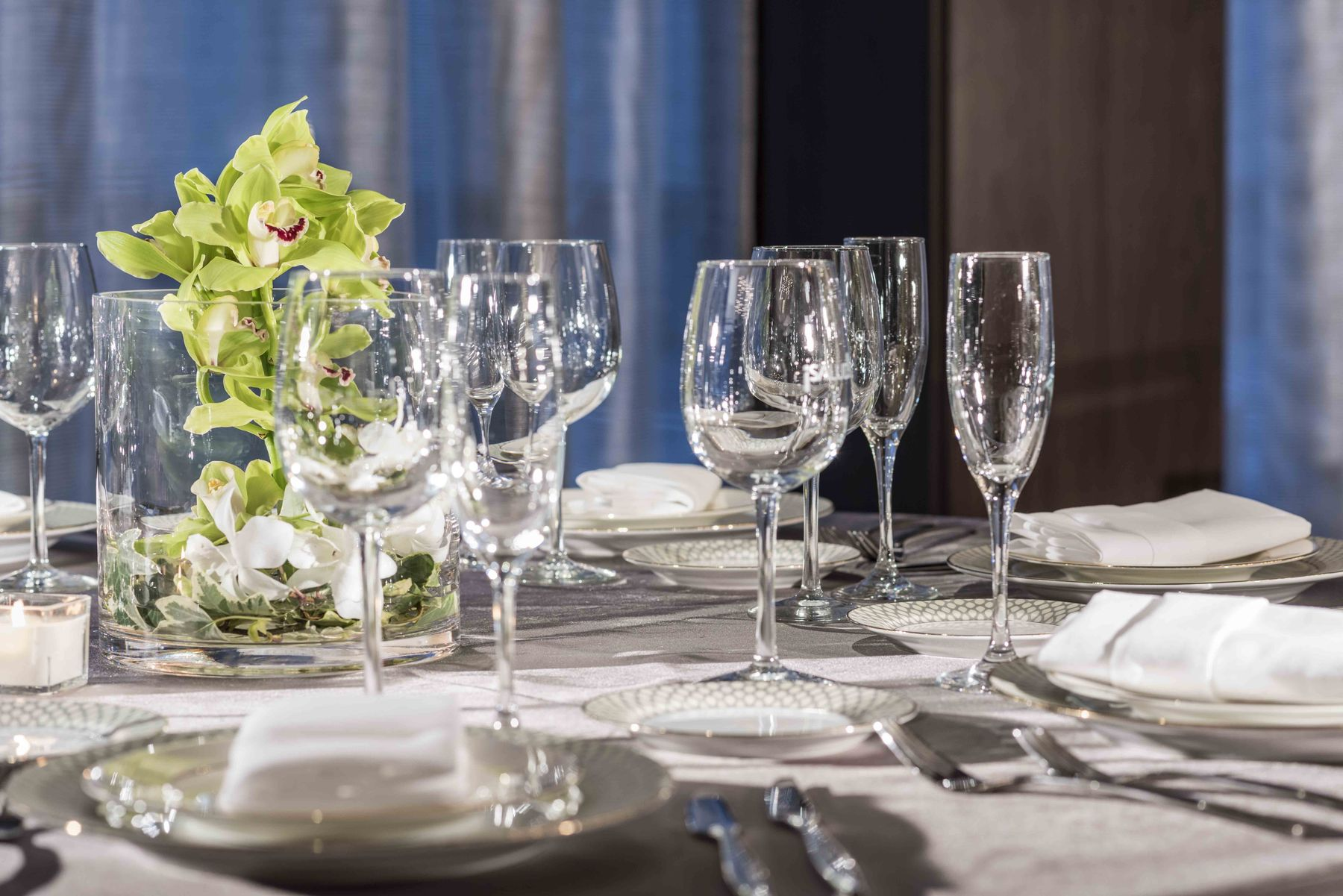 Formal place settings and floral arrangement on banquet table