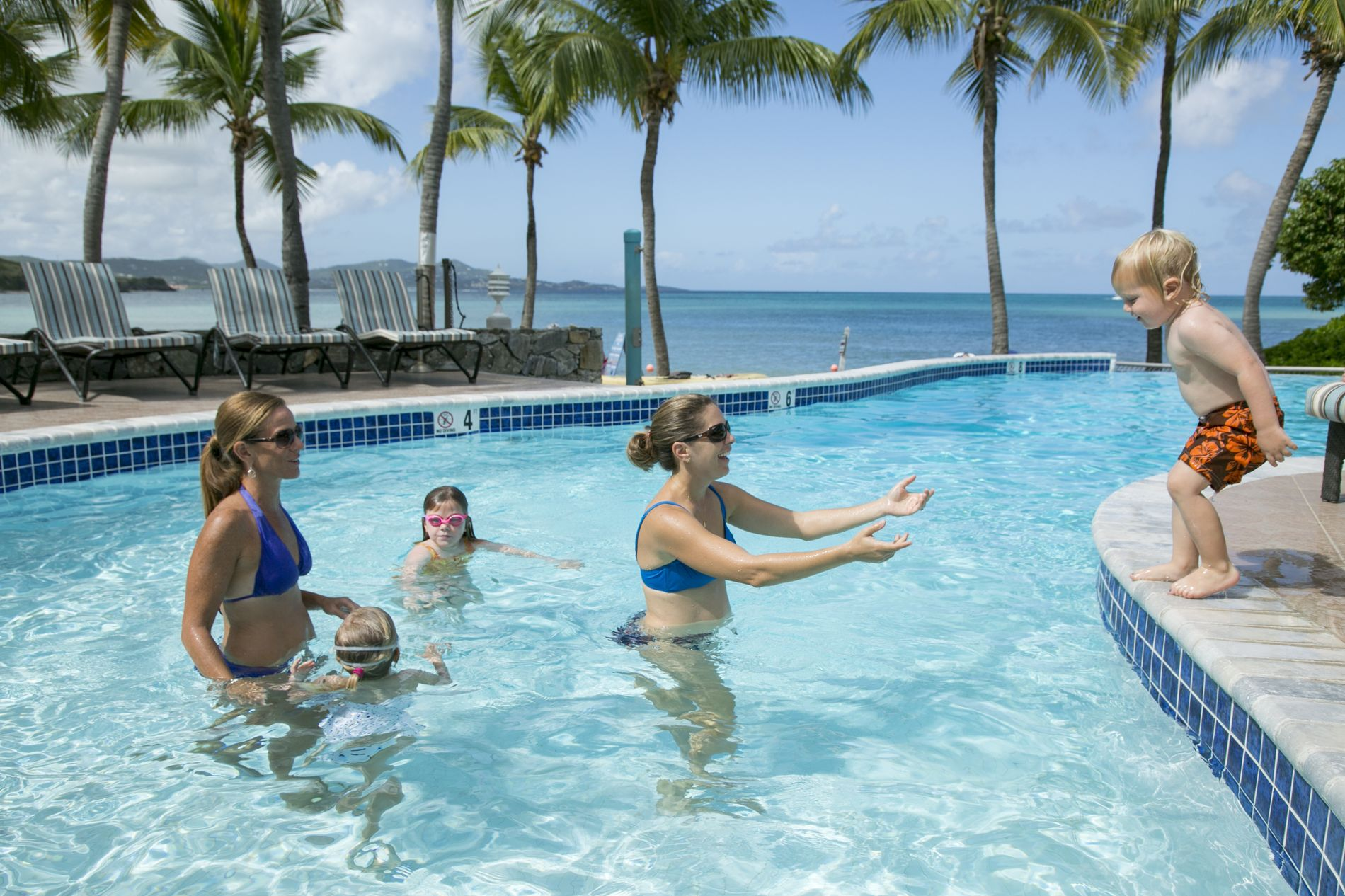 Family in Pool with little kid ready to jump in