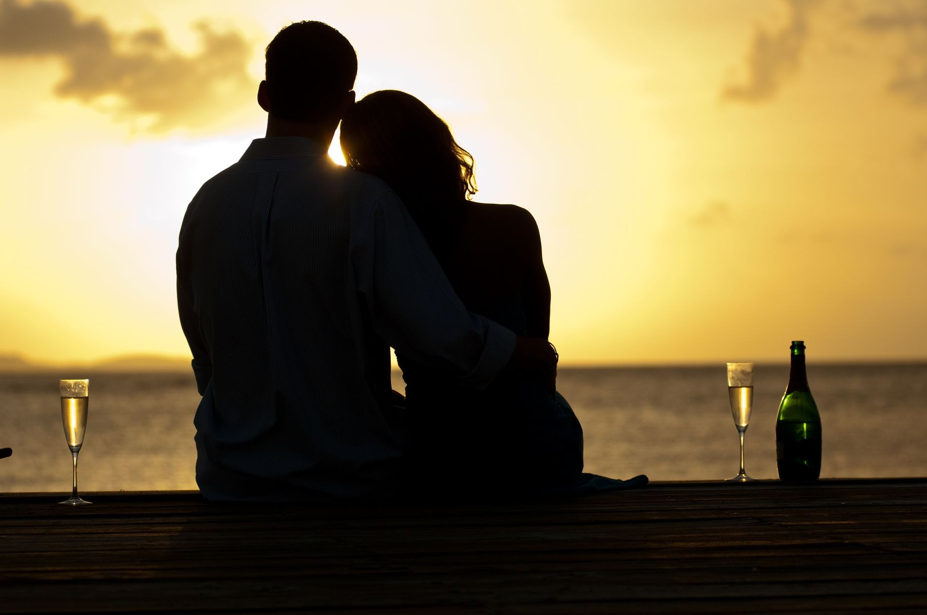 Couple holding each other on the beach at dusk next to champagne