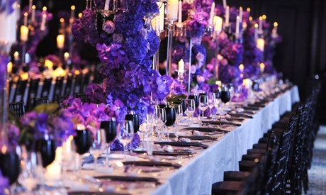 Long banquet table set for event with floral centerpieces