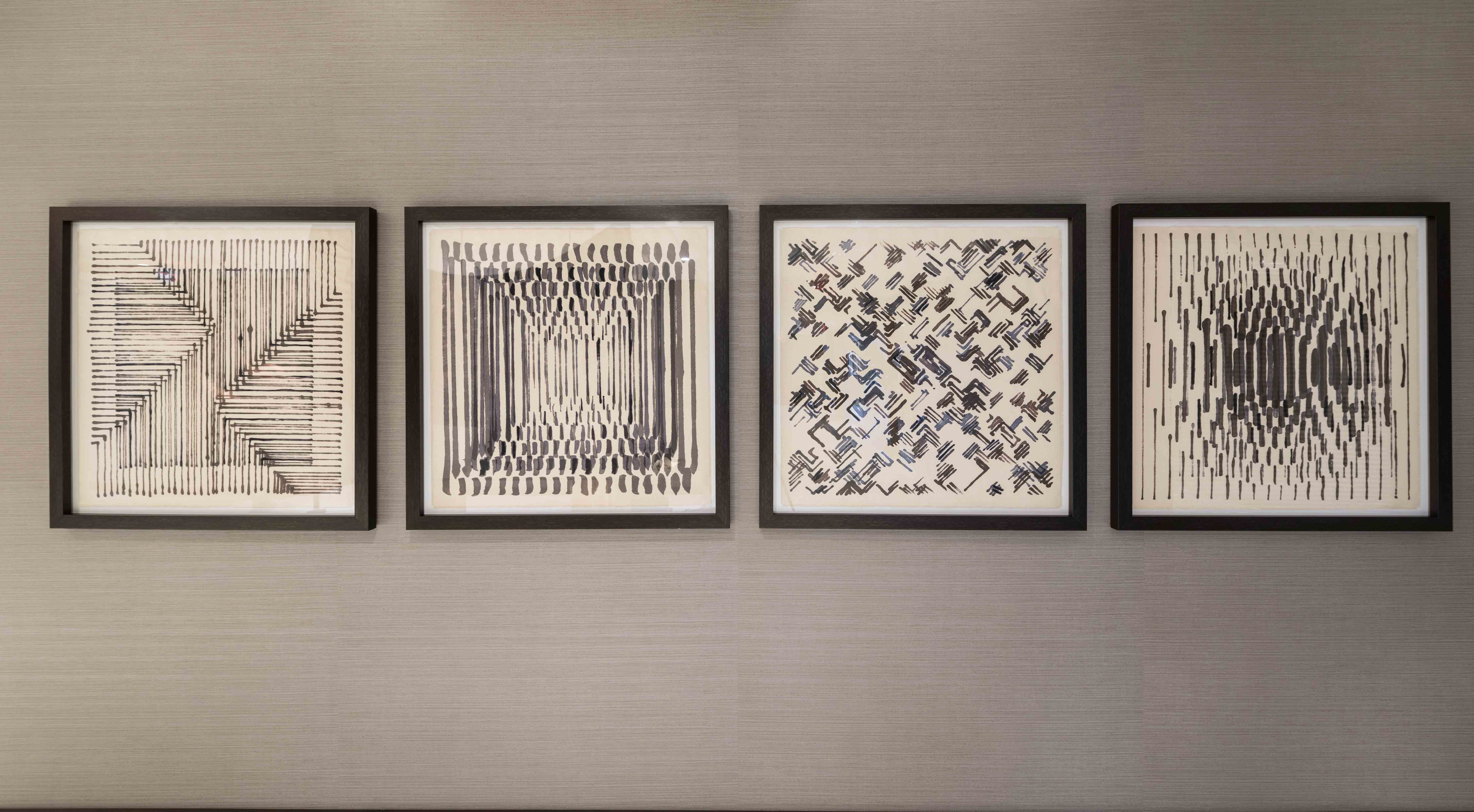Four pieces of geometric abstract art hanging on wall