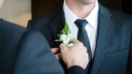 Man pinning boutonniere to lapel