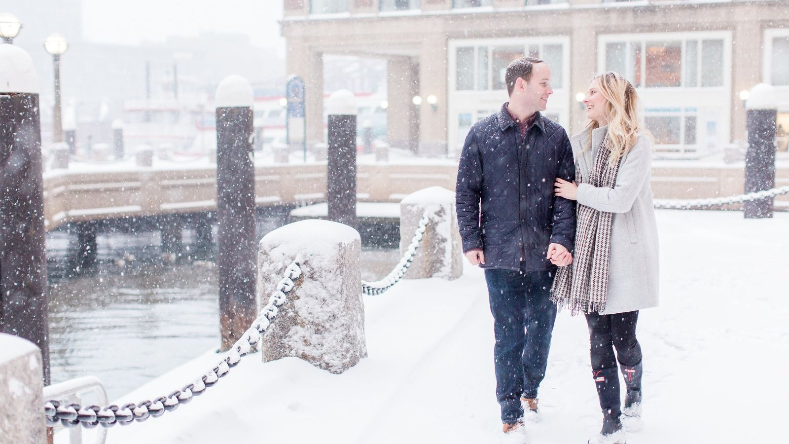 Happy couple walking in Boston Harbor snow