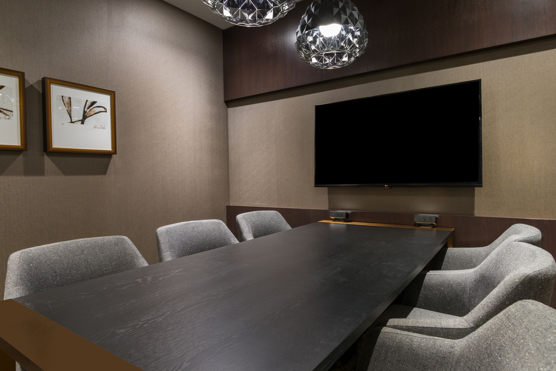 Conference table and chairs with TV mounted to wall