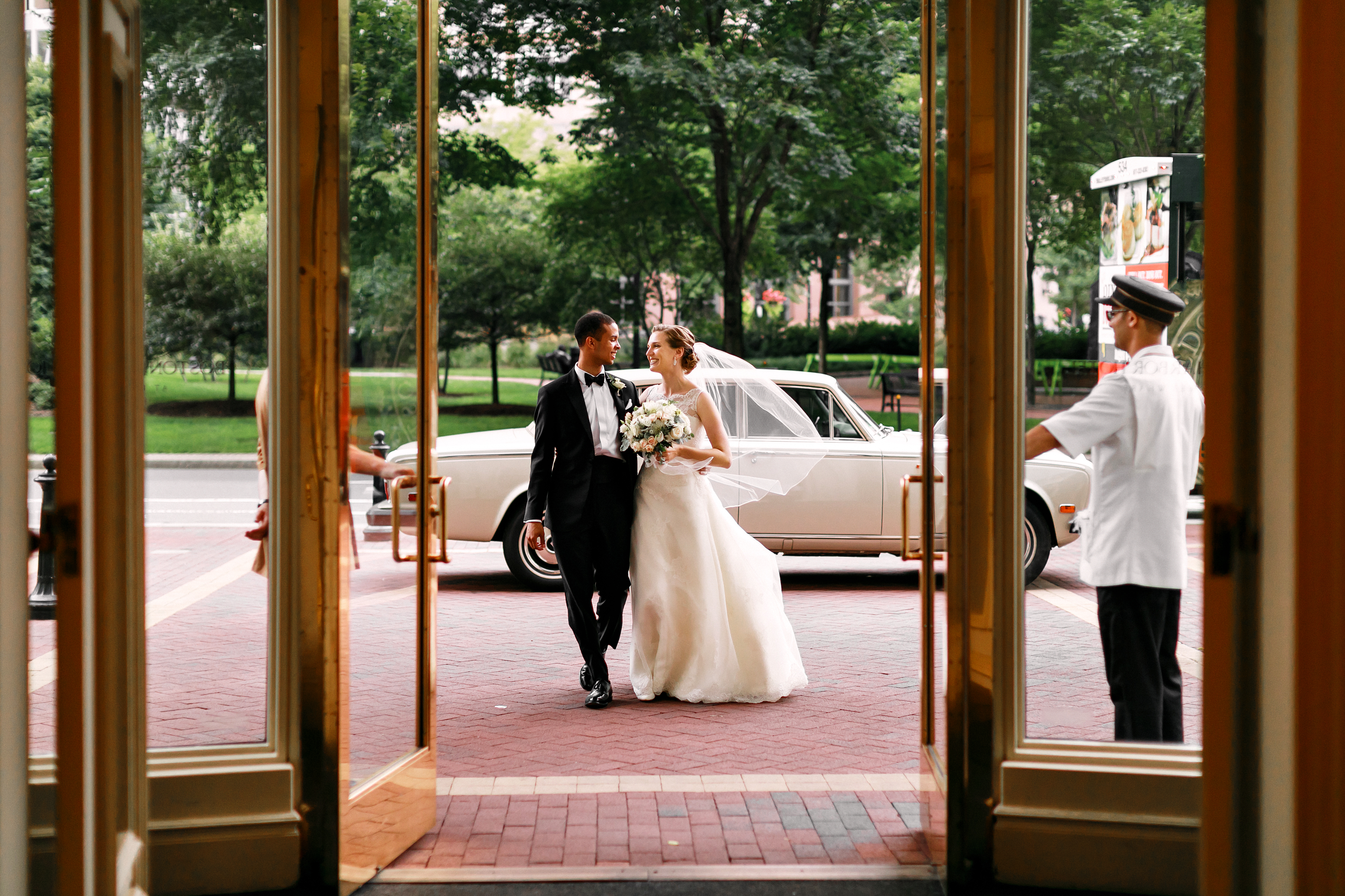 Newlyweds walking from their car to a grand hotel