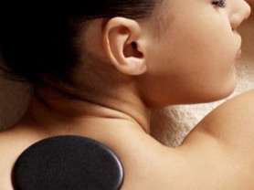 Woman with spa stones on her back