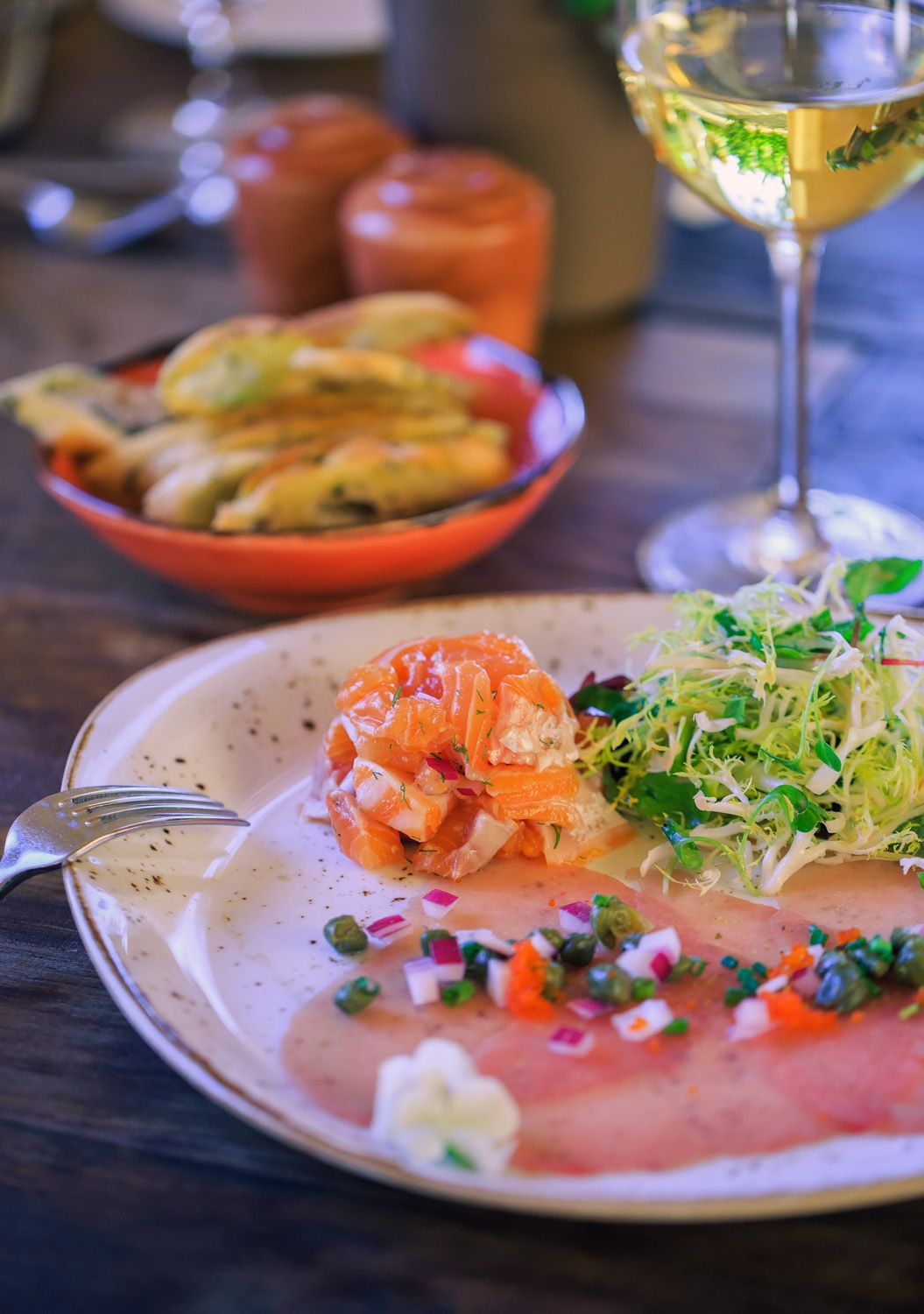 Bigeye Tuna Carpaccio accompanied by a glass of white wine prepa