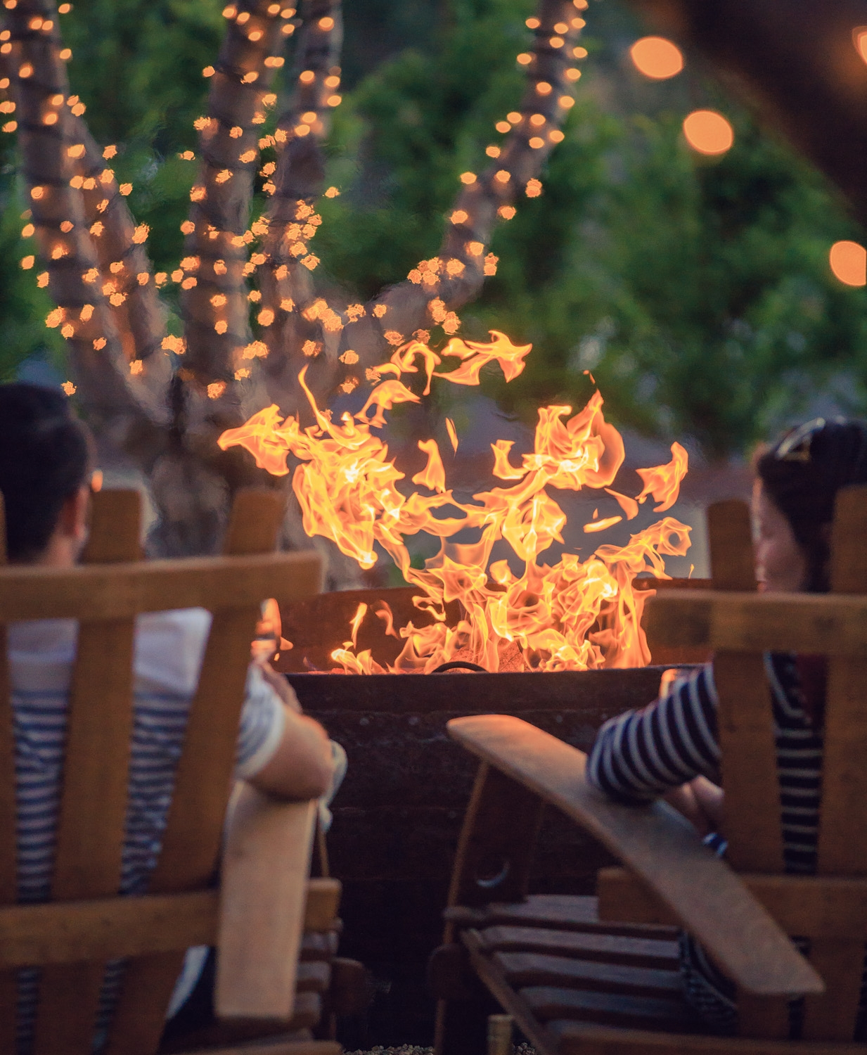 A man and woman sitting in wooden lounge chairs facing the fire