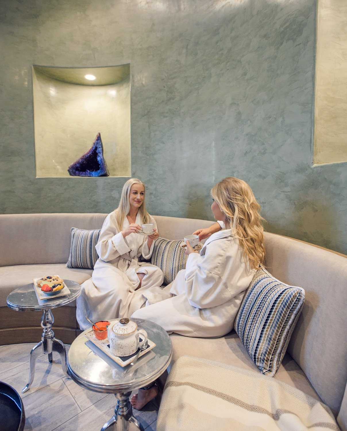 Two women lounging in their robes drinking tea
