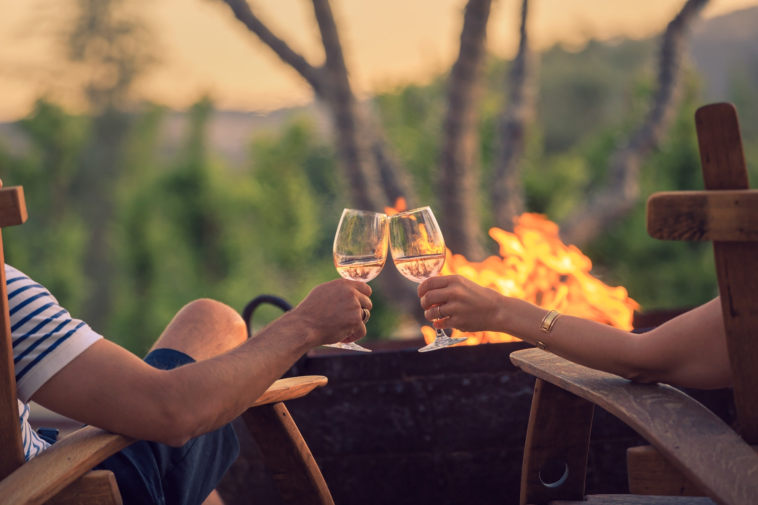 couple holding wine glasses while sitting near firepit