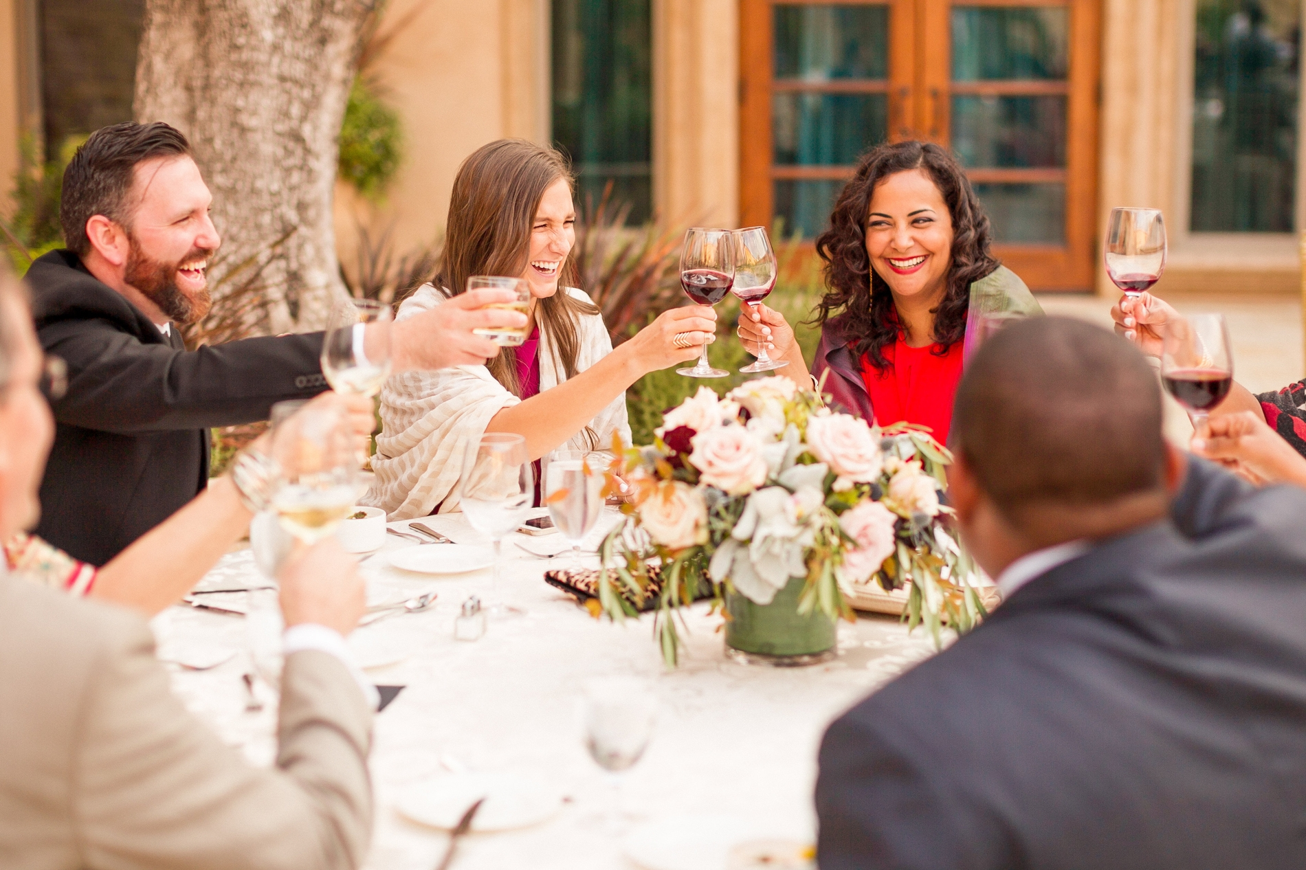 A wedding group tipping their glass around a round table and flo