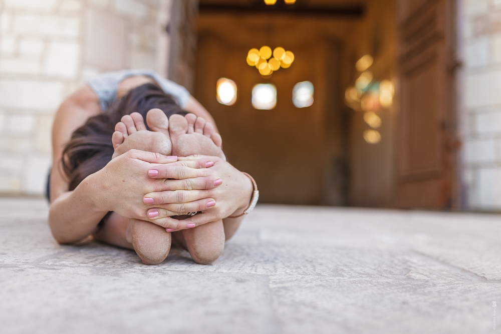 Woman stretching on the ground for Allegretto Yoga