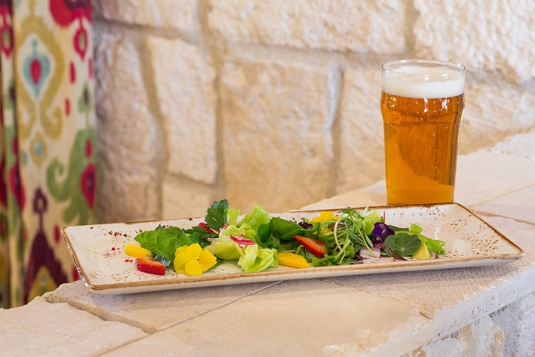 A salad accompanied by a cold beer at our Cello Restaurant