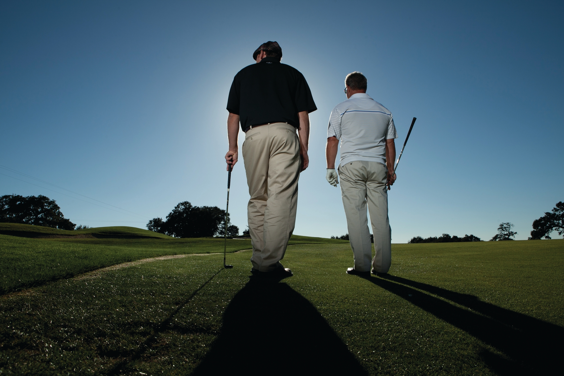 Two men standing on the fairway playing golf.  Blue sky and sunn
