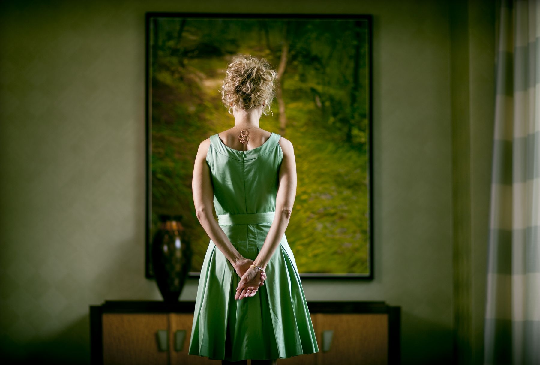 woman in green dress admiring painting