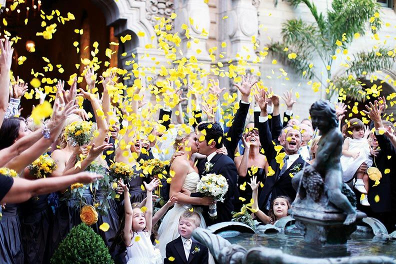 wedding party throwing yellow rose petals in the air