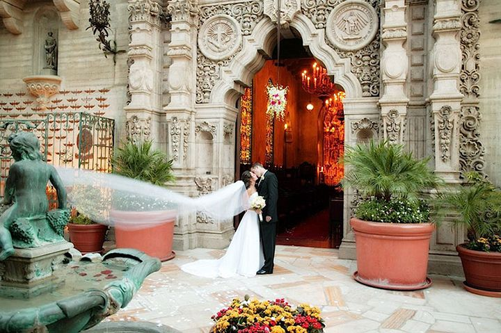 Bride and Groom kissing in front of entrance to St. Francis of A